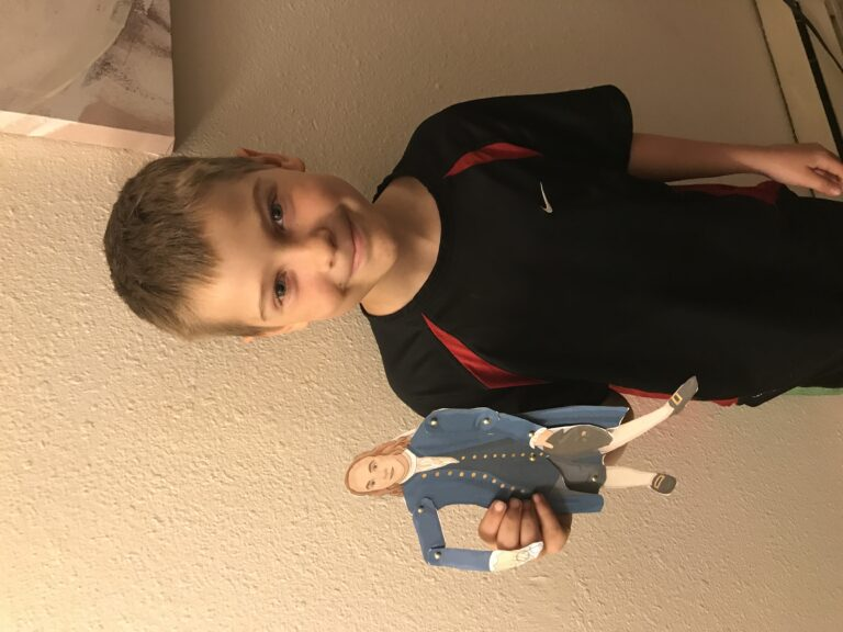 my 9-year-old son standing up and holding a paper doll of benjamin franklin