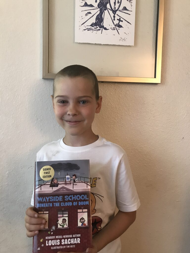 """my 9-year-old son standing up and holding his copy of the book """"wayside school beneath the cloud of doom"""""""