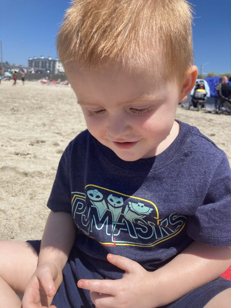 A 3-year-old little boy sitting on the beach. He is wearing a blue shirt that says PJ Masks and smiling at his sandy hands.